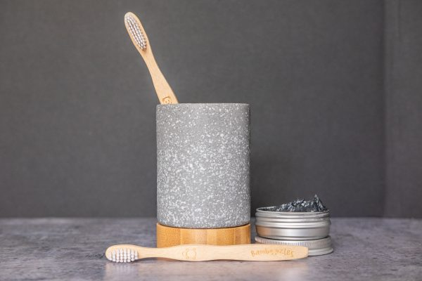bamboozles bamboo toothbrush in a holder with a 50g tin of natural charcoal whitening Toothpaste and kids bamboo toothbrush resting on front